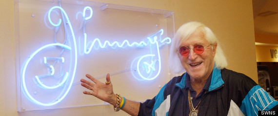 AYLESBURY, UNITED KINGDOM, OCTOBER 11, 2012; Sir Jimmy Savile outside the cafe named Jimmys - in the National Spinal Injuries Centre at Stoke Mandville Hospital - November 2005. See Masons story MNJIMMY. The NHS hospital where Jimmy Savile freely abused sick and disabled child patients knew 30 years ago he was a threat, it was claimed yesterday. Yet Stoke Mandeville chiefs allowed the predatory paedophile to boast he had his own bedroom at the Buckinghamshire hospital and had 'lived' there for two decades. Nurses even resorted to warning youngsters to 'pretend to be asleep' when the warped Jim'll Fix It star was approaching their wards, it was alleged. Yet while the BBC has issued a grovelling apology to the late presenter's many victims, NHS chiefs are refusing to say sorry.